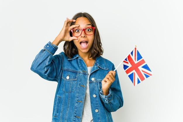 Молодая латинская женщина, держащая английский флаг, изолирована на белой стене, держа глаза открытыми, чтобы найти возможность успеха.