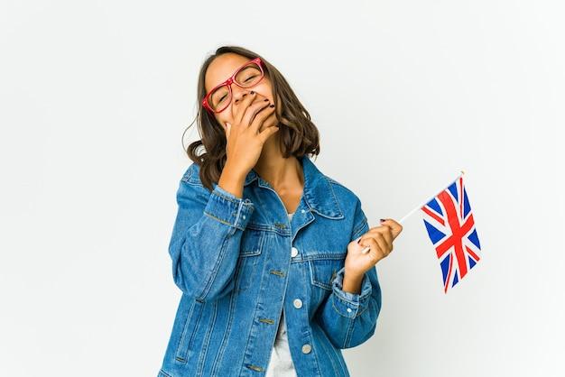 Молодая латинская женщина, держащая английский флаг, изолирована на белой стене, смеясь, счастливые, беззаботные, естественные эмоции.