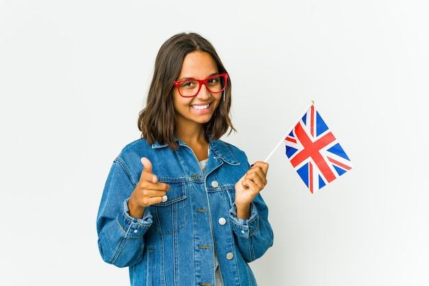 손가락으로 앞을 가리키는 흰 벽에 고립 된 영어 깃발을 들고 젊은 라틴 여자.