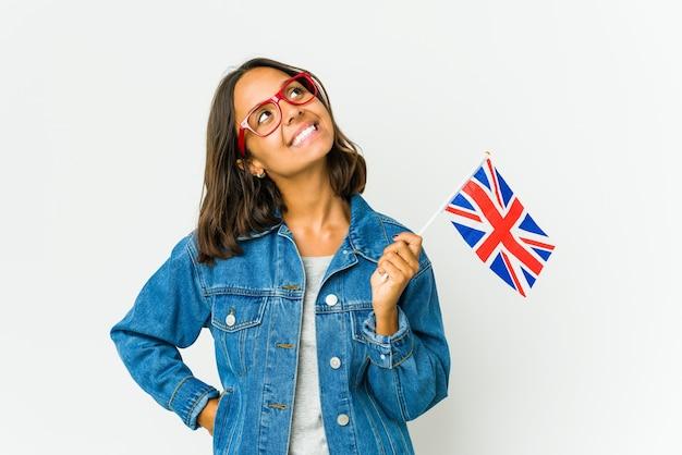 Молодая латинская женщина, держащая английский флаг, изолирована на белой стене, расслабилась и счастлива смеясь, вытянув шею, показывая зубы.