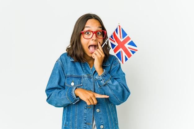 뭔가보고하는 측면을 가리키는 험담을 말하는 흰 벽에 고립 된 영어 깃발을 들고 젊은 라틴 여자.