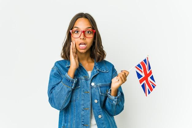 흰 벽에 고립 된 영어 깃발을 들고 젊은 라틴 여자 큰 소리로 외치고, 눈을 뜨고 손을 긴장시킵니다.