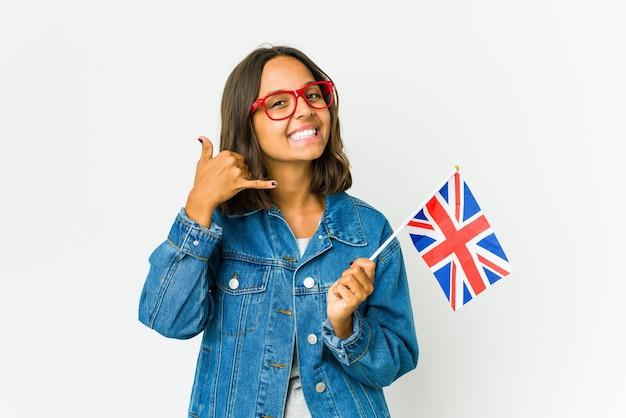 손가락으로 휴대 전화 제스처를 보여주는 흰 벽에 고립 된 영어 깃발을 들고 젊은 라틴 여자.