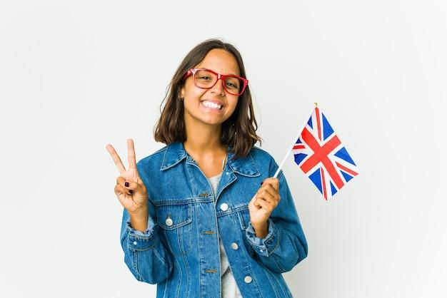 손가락으로 2 번을 보여주는 흰 벽에 고립 된 영어 깃발을 들고 젊은 라틴 여자.