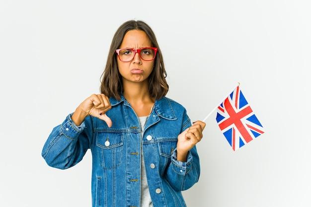 젊은 라틴 여자 아래로, 실망 개념 엄지 손가락을 보여주는 흰 벽에 고립 된 영어 깃발을 들고.