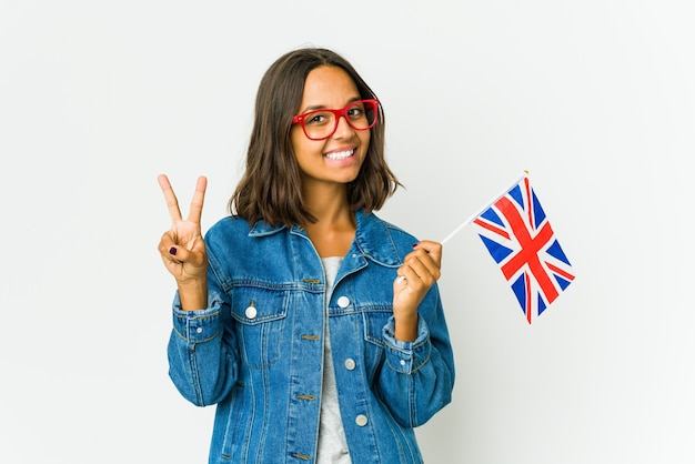 Молодая латинская женщина держит английский флаг, изолированную на белой стене, показывая знак победы и широко улыбаясь.