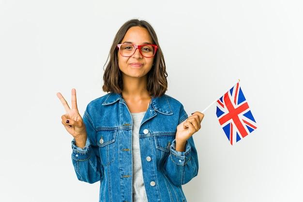 젊은 라틴 여자 가슴에 손을 넣어 맹세를 복용하는 흰 벽에 고립 된 영어 깃발을 들고.