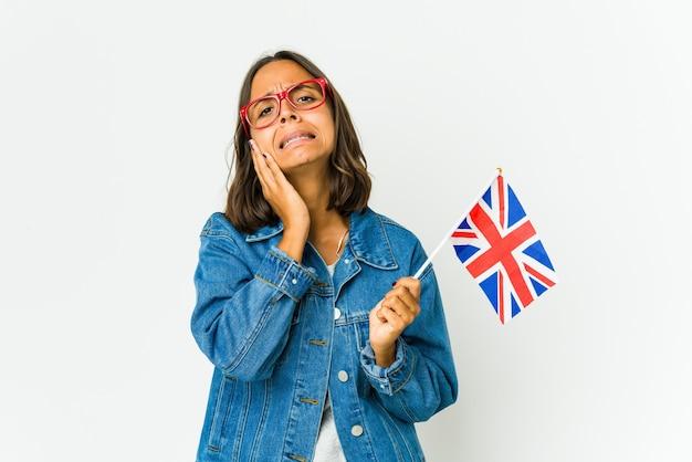 白い壁に孤立した英語の旗を持っている若いラテン女性が泣き叫び、悲しげに泣いています。