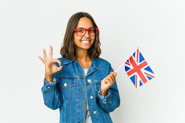 白で隔離の英語の旗を保持している若いラテン女性は目をまばたきし、手で大丈夫なジェスチャーを保持します。