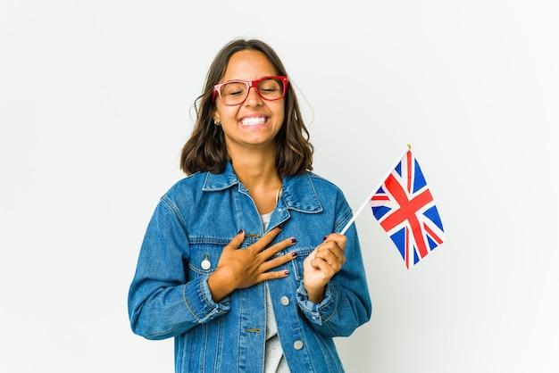 영어 국기를 들고 젊은 라틴 여자는 행복하게 웃고 뱃속에 손을 유지하는 재미가 있습니다.