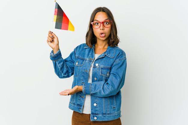 Молодая латинская женщина держит немецкий флаг, что-то держит обеими руками, презентация продукта.