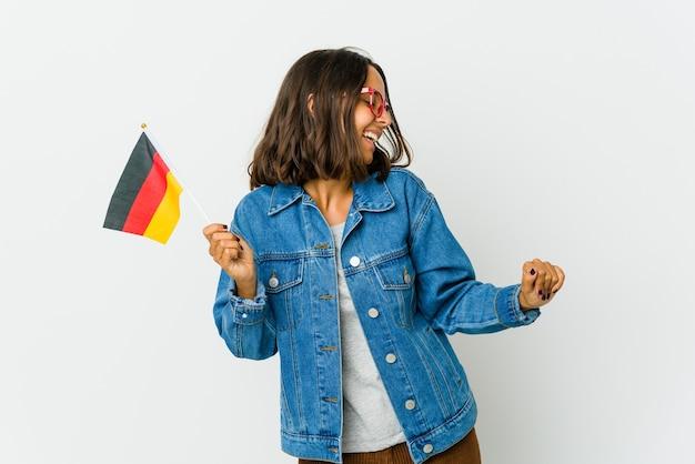 Молодая латинская женщина, держащая немецкий флаг на белом фоне, танцует и веселится.
