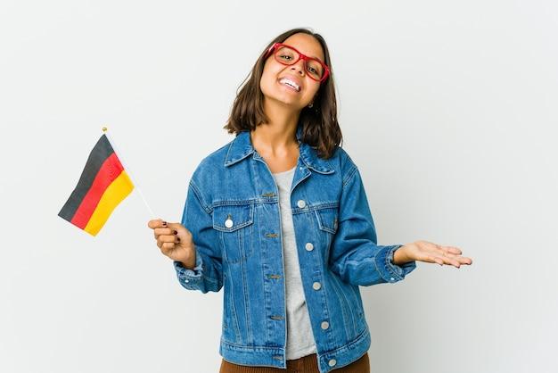 Молодая латинская женщина, держащая немецкий флаг на белом фоне, показывает приветственное выражение.