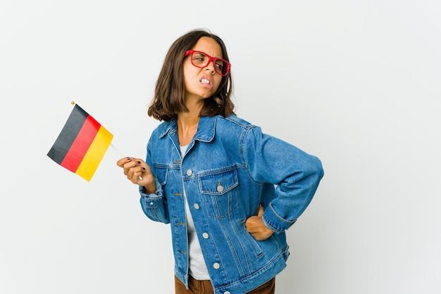 背中の痛みに苦しんで白い背景で隔離のドイツ国旗を保持している若いラテン女性。