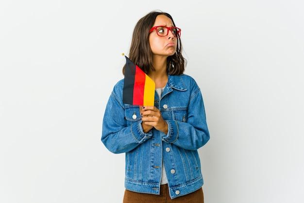 Молодая латинская женщина, держащая немецкий флаг, изолирована на белом, молясь, показывая преданность, религиозный человек, ищущий божественного вдохновения.