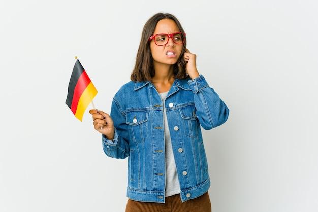 Молодая латинская женщина, держащая немецкий флаг, изолированная на белом пространстве, закрывающем уши пальцами, подчеркнута и отчаянна из-за громкого окружения.