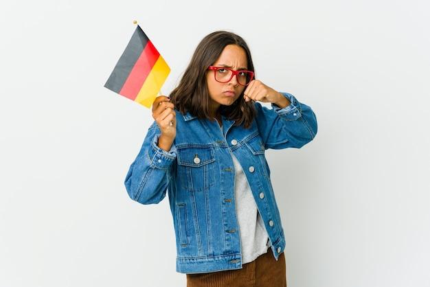 Молодая латинская женщина, держащая немецкий флаг, изолированная на белом, бросает удар, гнев, борьба из-за спора, бокс.