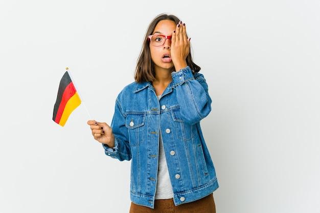 Молодая латинская женщина, держащая немецкий флаг, изолирована на белой стене, весело закрывая половину лица ладонью.