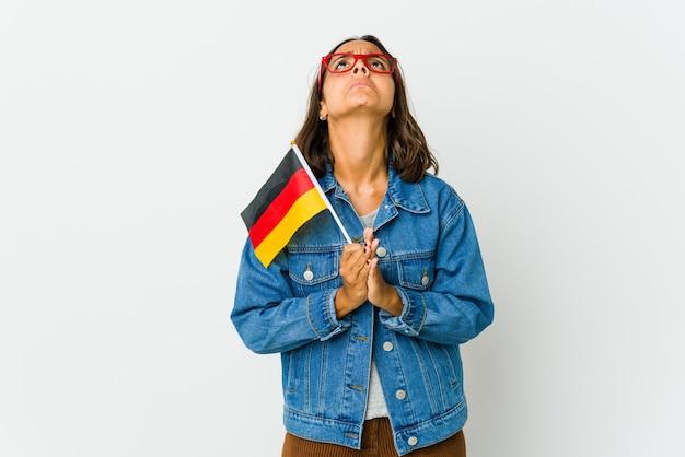 Молодая латинская женщина, держащая немецкий флаг, изолированную на белой стене, взявшись за руки в молитве возле рта, чувствует себя уверенно.