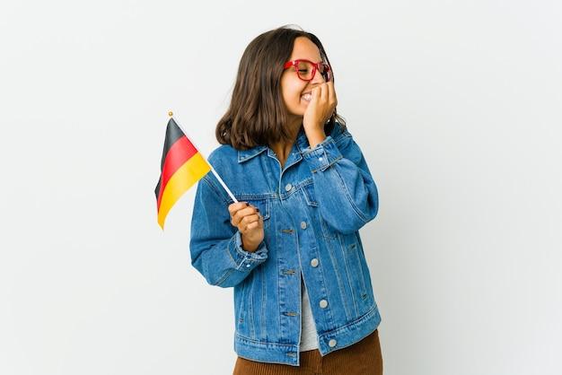 Молодая латинская женщина, держащая немецкий флаг, изолированная на белой стене, смеется о чем-то, прикрывая рот руками.