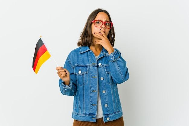 Молодая латинская женщина, держащая немецкий флаг, изолированную на белой стене, испугалась и испугалась.