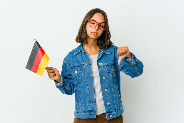 Молодая латинская женщина держит немецкий флаг, изолированную на белой стене, показывая жест неприязни, пальцы вниз. концепция несогласия.