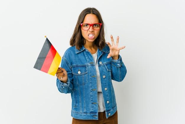 Молодая латинская женщина, держащая немецкий флаг, изолирована на белой стене, показывая когти, имитирующие кошку, агрессивный жест.