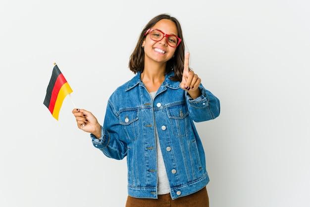 Молодая латинская женщина держит немецкий флаг, изолированную на белой стене, показывая пальцем номер один