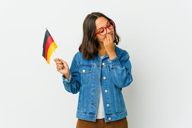 Молодая латинская женщина, держащая немецкий флаг, расслабилась, думая о чем-то, глядя на копию пространства.