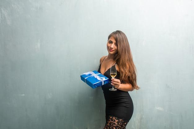 선물 및 샴페인 컵을 들고 젊은 라틴 여자, 그녀는 재미있다.