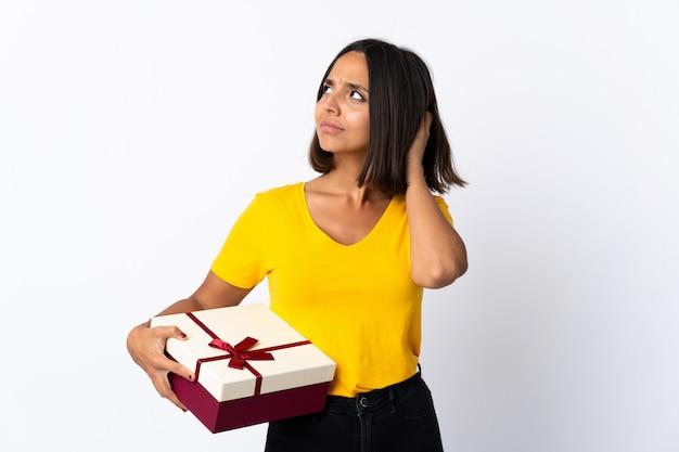 Молодая латинская женщина держа подарок изолированный на белизне имея сомнения