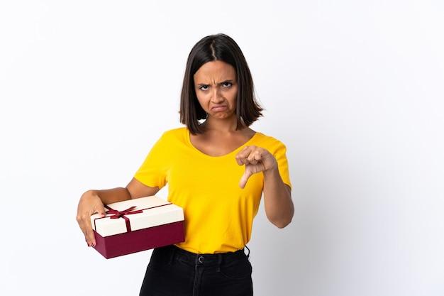 否定的な表現でダウン親指を示す白で隔離されるギフトを保持している若いラテン女性
