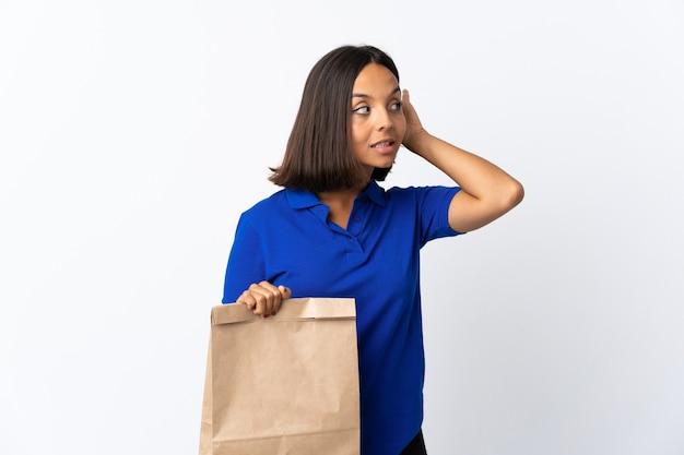귀에 손을 넣어 뭔가를 듣고 흰색 배경에 고립 된 식료품 쇼핑 가방을 들고 젊은 라틴 여자