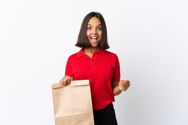 Молодая латинская женщина держа сумку посещения магазина бакалеи изолированная на белизне празднуя победу в положении победителя
