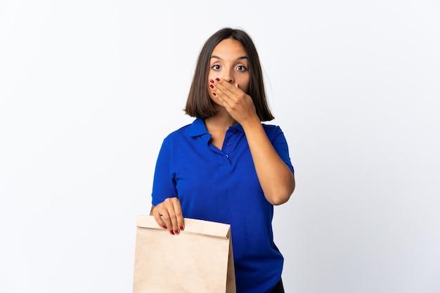 手で白い円錐形の口に分離された食料品の買い物袋を保持している若いラテン女性