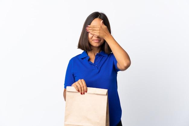 Молодая латинская женщина, держащая продуктовый мешок, изолированные на белом, закрыв глаза руками
