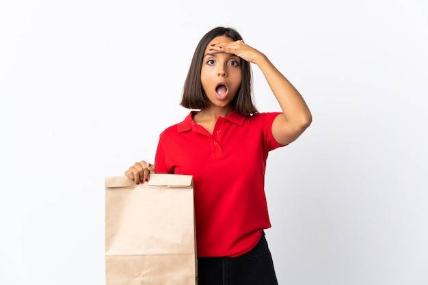 Молодая латинская женщина держа сумку посещения магазина бакалеи изолированная на белизне делая жест сюрприза пока смотрящ в сторону