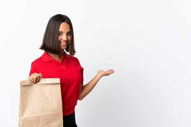 Молодая латинская женщина, держащая сумку для покупок, изолированная на белом, протягивающая руки в сторону для приглашения прийти
