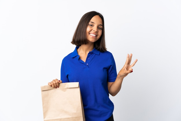 Молодая латинская женщина держа продуктовую хозяйственную сумку изолированный на белом счастливом и подсчитывая 3 с пальцами