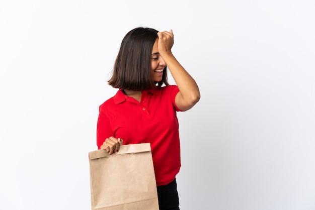 Молодая латинская женщина с продуктовой сумкой, изолированная на белом, что-то поняла и намеревается найти решение