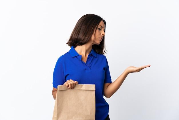 Молодая латинская женщина держа сумку посещения магазина бакалеи изолированная на белизне держа copyspace с сомнениями