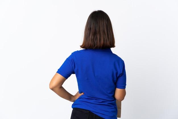 Молодая женщина латинской, держа сумку продуктовых магазинов, изолированных на белом в задней позиции
