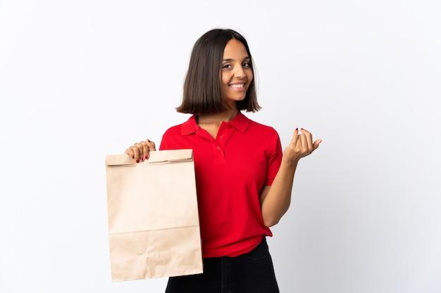 Молодая латинская женщина держа сумку посещения магазина бакалеи изолированный на белизне приглашая прийти с рукой. счастлив, что ты пришел