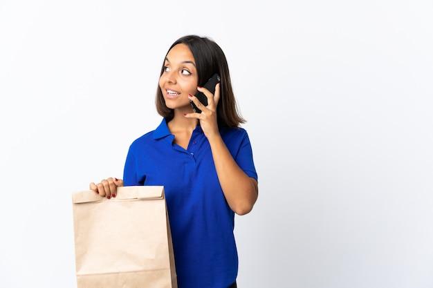 Молодая латинская женщина, держащая продуктовый пакет, изолирована на белом, ведя разговор с кем-то по мобильному телефону