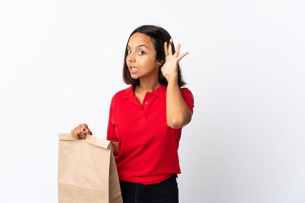 耳に手を置くことで何かを聞いて白で隔離される食料品の買い物袋を保持している若いラテン女性