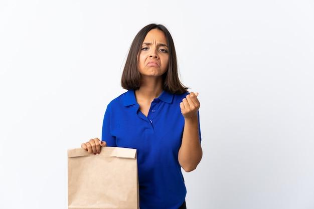 Молодая латинская женщина держа сумку посещения магазина бакалеи изолированная на белизне делая итальянский жест