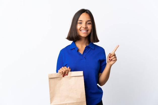 Молодая латинская женщина держа сумку посещения магазина бакалеи изолированная на белизне указывая вверх по отличной идее