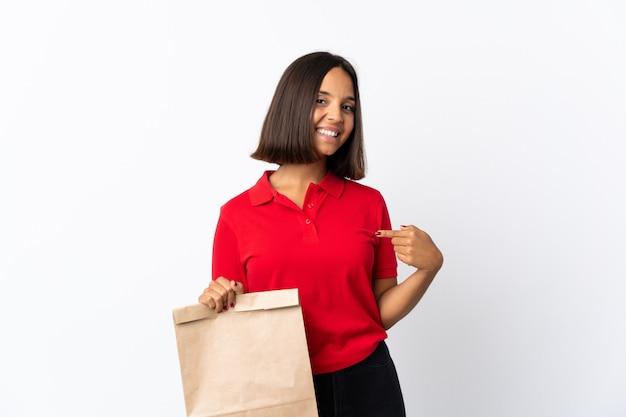 Молодая латинская женщина держа сумку посещения магазина бакалеи изолированная на белизне гордая и самодовольная