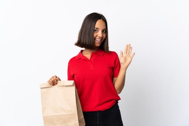 Молодая латинская женщина держа сумку посещения магазина бакалеи изолированная на белизне салютуя с рукой с счастливым выражением
