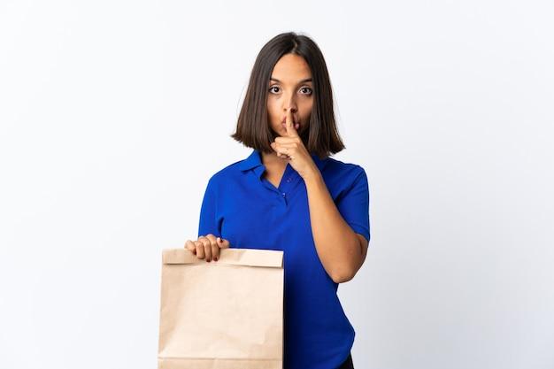 白で隔離の食料品の買い物袋を持っている若いラテン女性は、口に指を入れて沈黙のジェスチャーの兆候を示しています